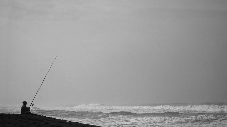 Silhouette of man fishing by the sea. sitting alone holding the long fishing rod.