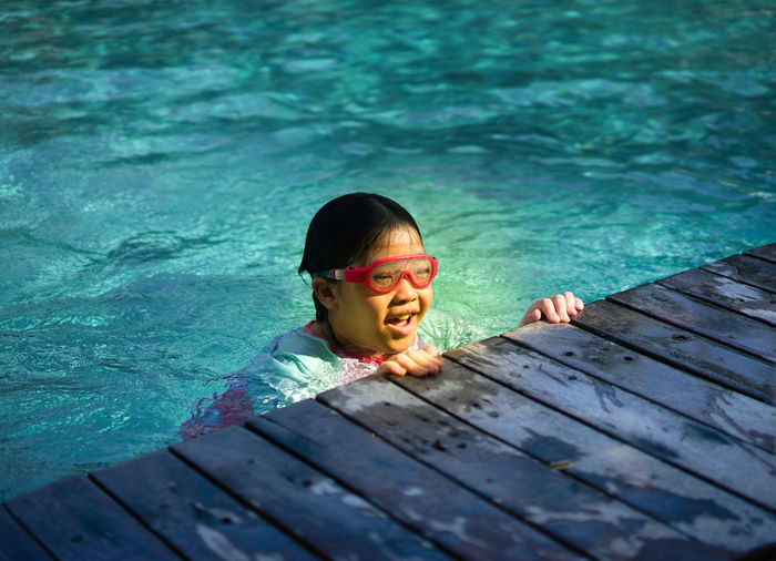 Portrait of girl at poolside of swimming in pool