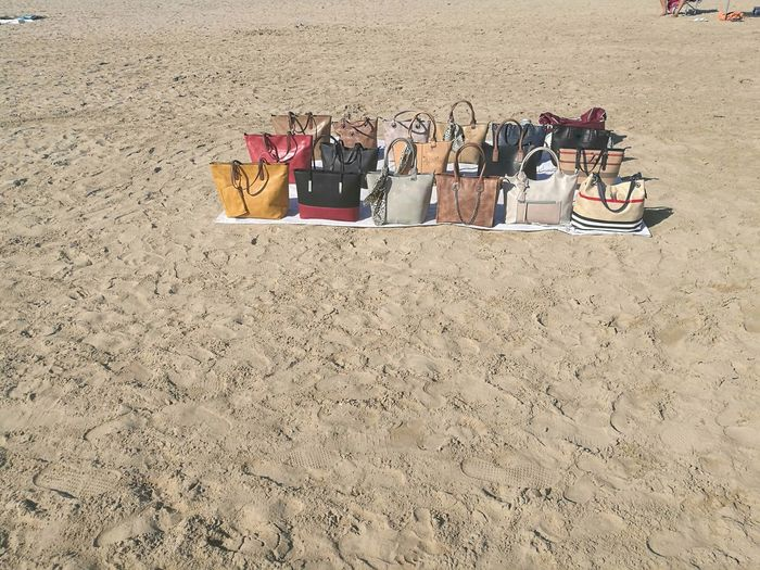 Counterfeit bags for sale on the beach Branded Sale Abundance Bags Beach Day Fake False Illegal Large Group Of Objects No People Outdoors Sand Sand Pail And Shovel Seller Vendor
