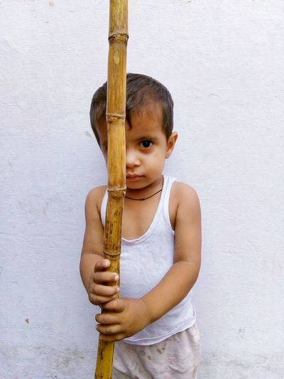 Portrait of a little angry young child holding Lathi Fighter Portrait Asian  Furious Pride Frowning Angery Lathi Holding Kid Indian Culture  Looking At Camera Displaced Frustration Sulking Confidence  Reddy To Fight Grimacing Distraught  Cuteness Indian Child Childhood Facial Expression Portrait Making A Face Thoughtful Innocence Babyhood Winking The Portraitist - 2018 EyeEm Awards A New Beginning
