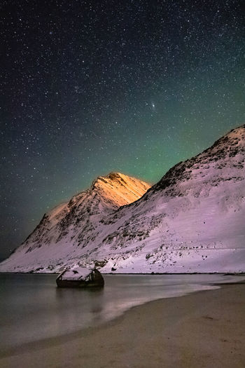 Scenic view of beach and mountains against sky at night