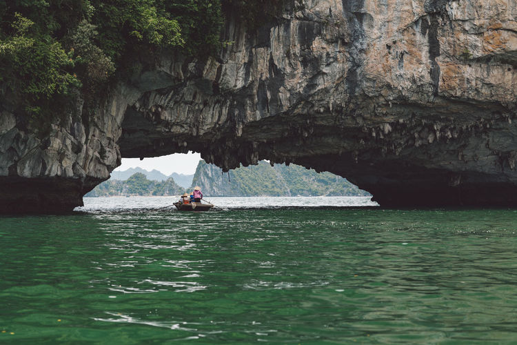 People Rowing Boat On Halong Bay Under Rock Formation