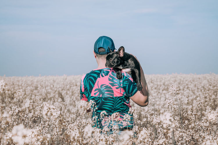 Nature Field Flowering Plant Canola Canola Field Pink One Person One Man Only Men Holding Rear View Frenchie French Bulldog Frenchbulldog Puppy Canine One Animal Animal Animal Themes Pets Portrait Togetherness Rural Scene Summer Dog Bonding Boho Growing Hippie Posing Springtime Decadence