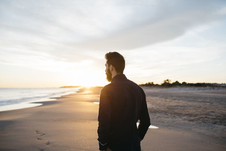Rear view of mid adult man standing at beach against cloudy sky during sunset