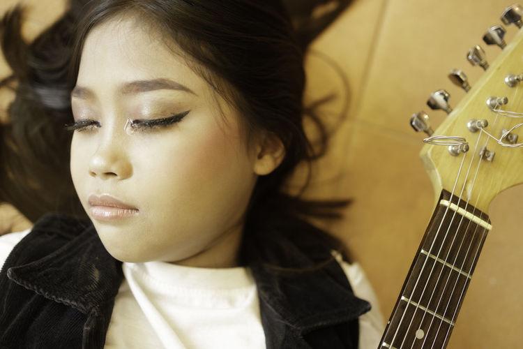 Close-up of teenage girl playing guitar