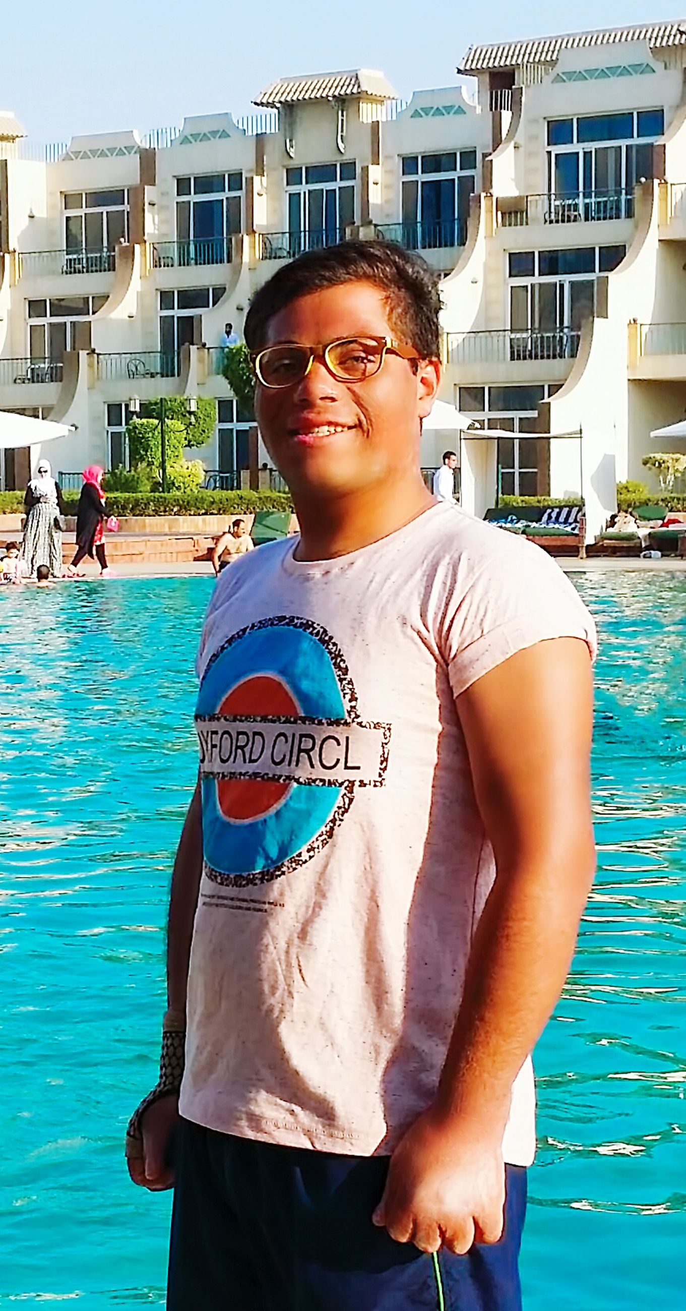 person, water, lifestyles, looking at camera, building exterior, portrait, built structure, young adult, leisure activity, front view, smiling, casual clothing, architecture, blue, swimming pool, happiness, three quarter length, standing