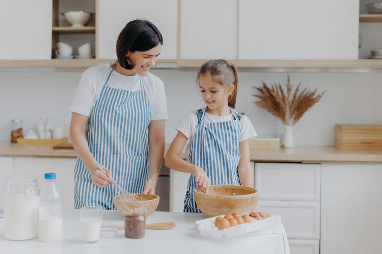 Women and daughter in kitchen at home