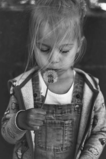 Portrait of cute girl with dandelion