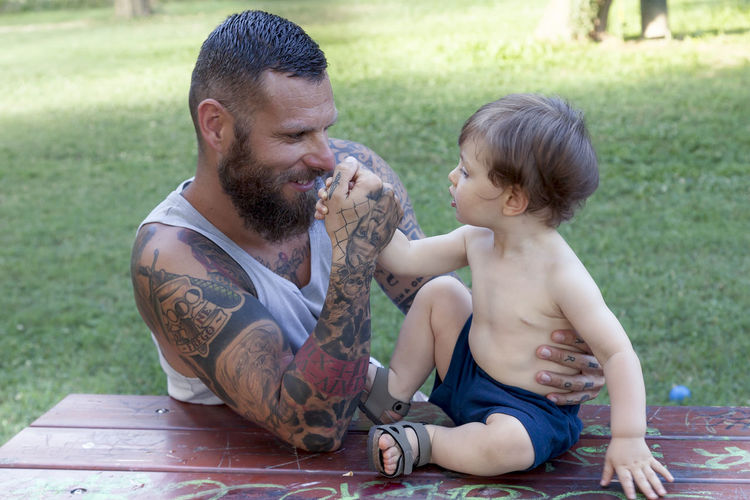 Smiling bearded man arm wresting with son sitting on picnic table
