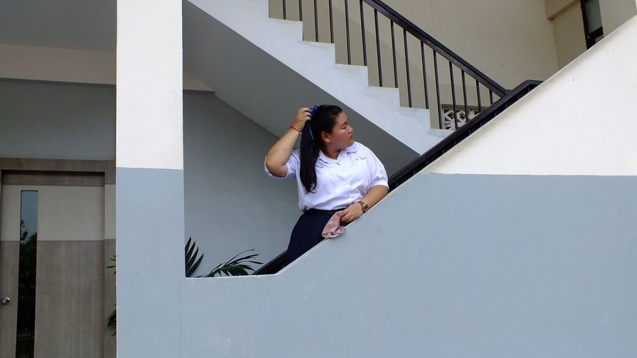 Teenage girl in school uniform standing on staircase of building