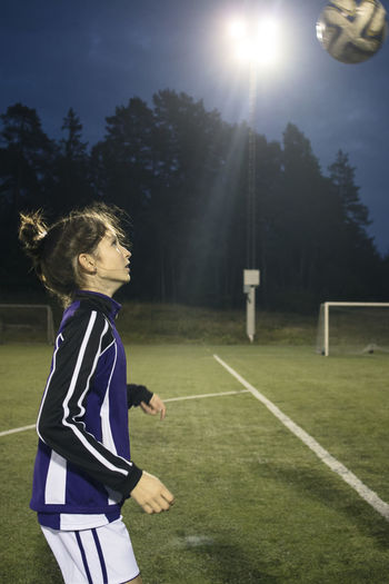 Side view of girl playing on soccer field
