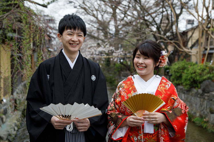 Marriage in Kyoto, Japan Kyoto Marriage  Bride Kimono Young Adult Smile Fan Japan Smiling Two People Front View Togetherness Men Looking At Camera Child Standing Happiness Emotion Waist Up Clothing Holding Portrait Women Celebration Toothy Smile Outdoors