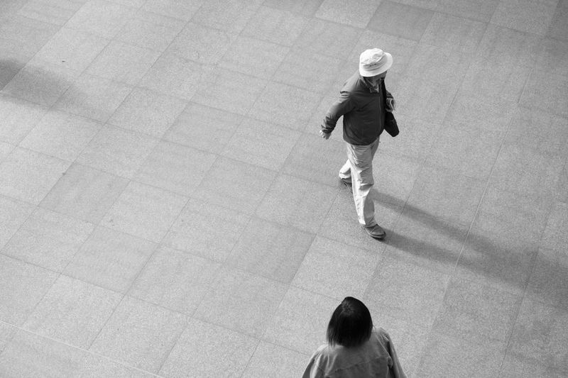 Man in a white hat and jacket and an Asian woman walk through a train station in Europe. Looking down on two people from above, black and white image. Antwerp Antwerp Central Station Antwerp, Belgium Antwerpen Antwerpen Centraal Antwerpen, Belgium Adult Adults Only Antwerp Belgium Day Full Length Indoors  People Train Station Train Station Platform Train Stations Walking Young Adult