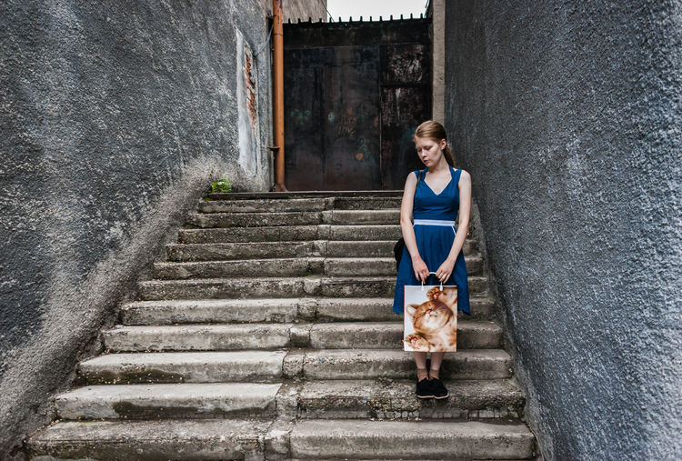 Serious teenage girl looking down on stairs