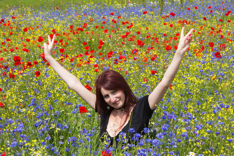 Portrait of smiling woman with arms raised amidst flowers on field