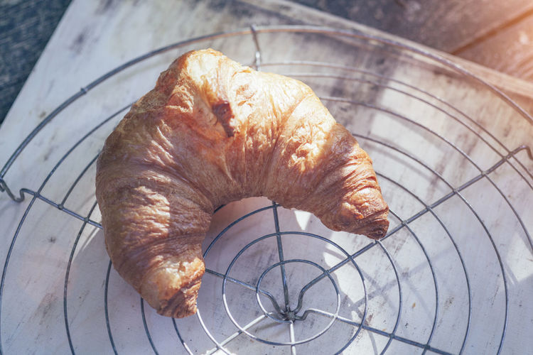 High angle view of croissant on cooling rack over table