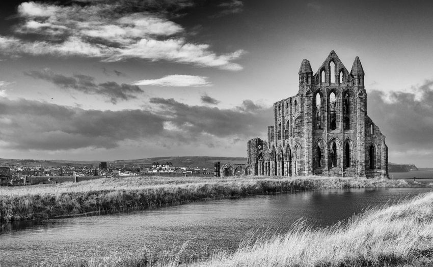 Whitby Abbey, North Yorkshire, UK with a lake in the foreground and the town in the distance. Sky Architecture Built Structure Water Building Exterior Cloud - Sky History The Past Nature Grass Place Of Worship Day Building Old Ruin Religion No People Travel Destinations Ancient Ruined Outdoors Abbey Ancient Civilization Black And White Monochrome Abbey