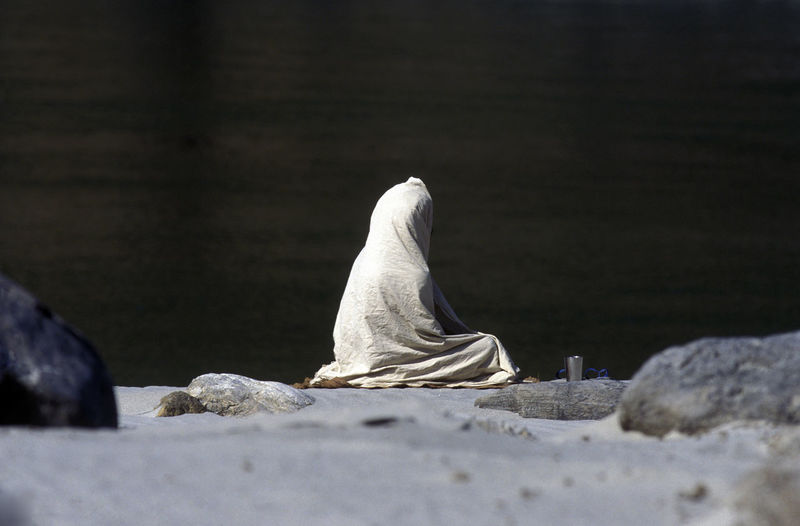 Beggar Covered With Blanket While Sitting On Rock