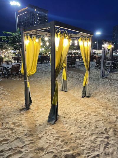 Illuminated yellow lights on beach against sky at night