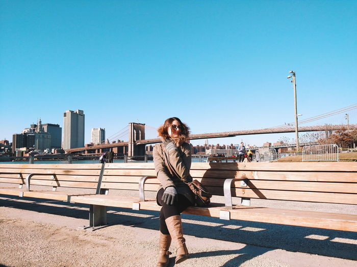 Portrait of smiling young woman standing against clear sky on sunny day