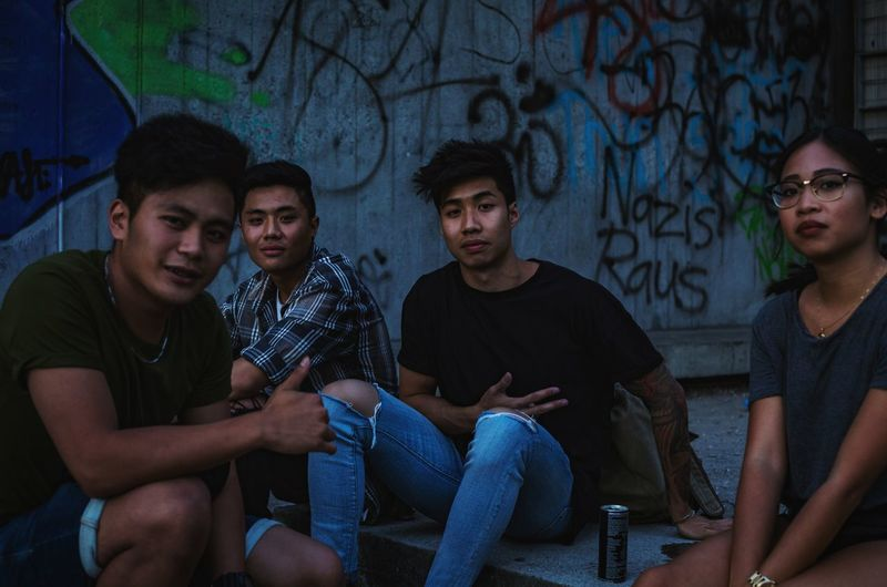 Squad. Sitting Adult Mid Adult Mid Adult Men People Young Adult Social Issues Talking Adults Only Young Men Candid Togetherness Men Night Real People Young Women Outdoors Friendship City