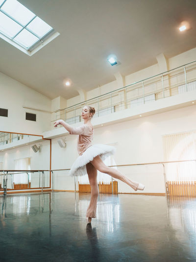 Young attractive blonde woman in white tutu clothing practicing in classical ballet in the gym. Minimalism interior, dancing sensual dance. Ballerina Arts Culture And Entertainment Ballet Ballet Dancer Ballet Shoes Ballet Studio Ceiling Dance Studio Dancing Flooring Full Length Human Arm Illuminated Indoors  Lifestyles One Person Performance Practicing Real People Skill  Standing Tiptoe Women Young Adult Young Women