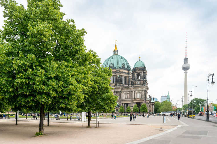 Berlin cathedral by fernsehturm tower against sky