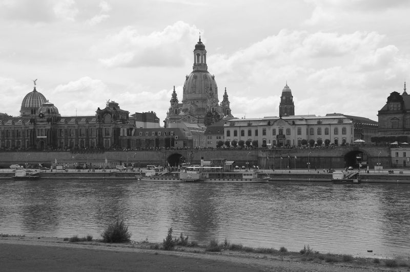 River by buildings and dresden frauenkirche against cloudy sky