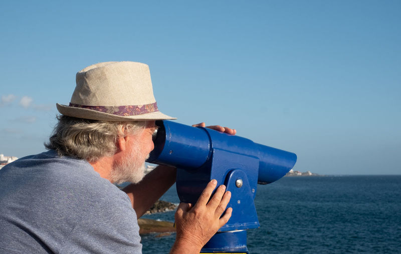 Man wearing hat against sea against clear sky