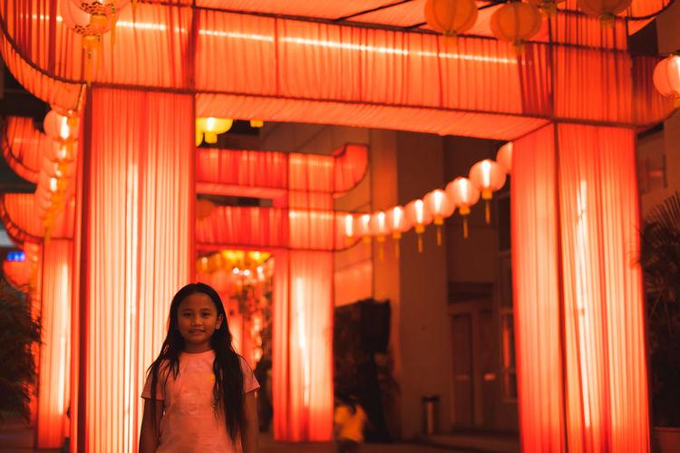 Portrait of girl standing against illuminated decoration