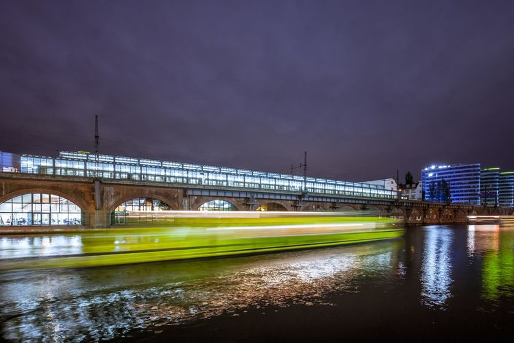 Blurred Image Of Boat In Spree River Against Railroad Station At Night