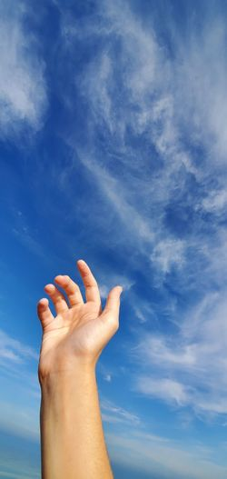 Low angle view of man hand against blue sky