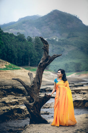 Full length of woman standing by tree against mountain