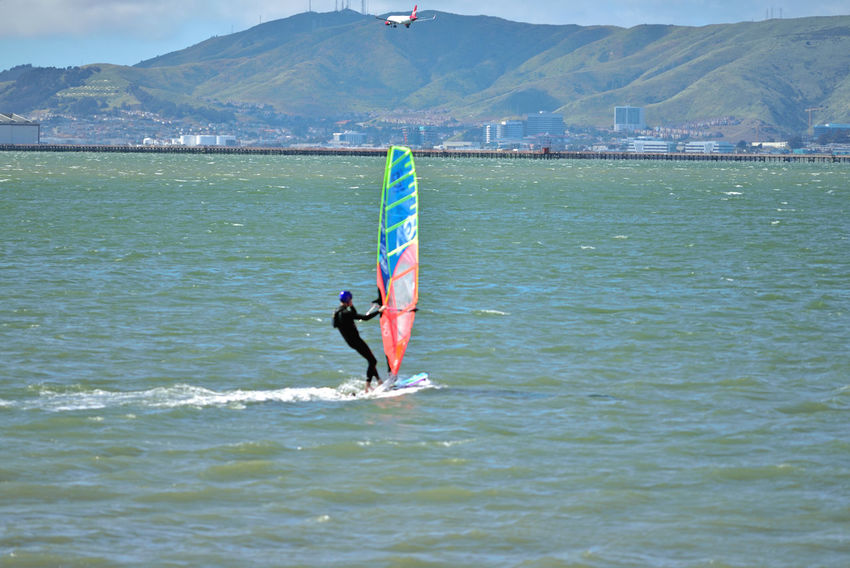 Windsurfing At Coyote Point 12 Windsurfer Windsurfing Riding The Winds Wake Coyote Point San Francisco Bay Airplane Final Approach To SFO Hills Of San Francisco Office Buildings Sports Photography Motion Aquactic Sports Pier Landscape_Collection Landscape Photography A Day On The Bay Enjoying Life Wetsuit Wind Sail Extreme Sports Water Athlete Adventure Wave Mountain Sportsman Surfing Water Sport Surfboard