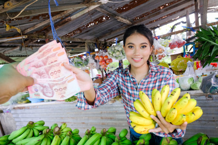 Portrait of smiling young woman holding fruits