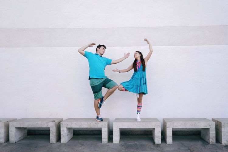 Couple Dancing On Seats Against Wall