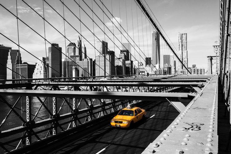 Taxi on brooklyn bridge against manhattan skyline