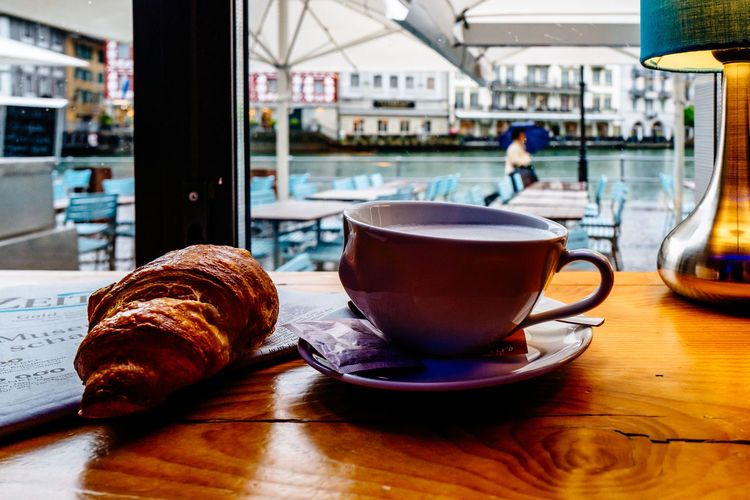Close-up of coffee cup with croissant on table in restaurant