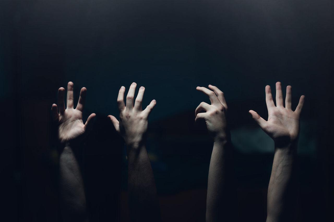 Cropped hands of people gesturing in darkroom
