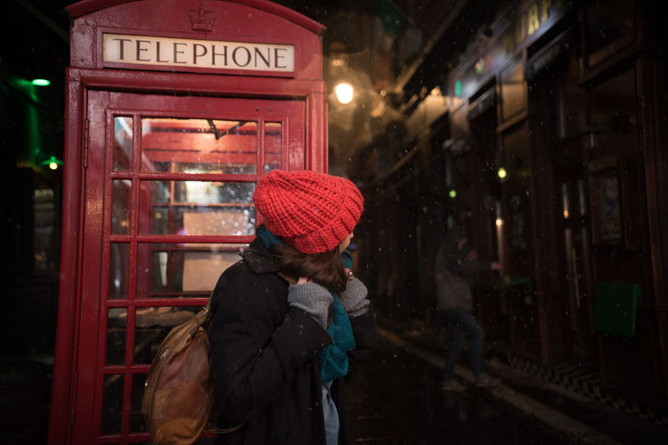 Woman Standing Against Telephone Booth At Night