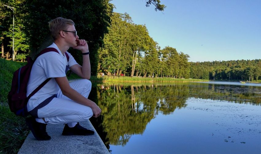 Side view full length of young man crouching by calm lake