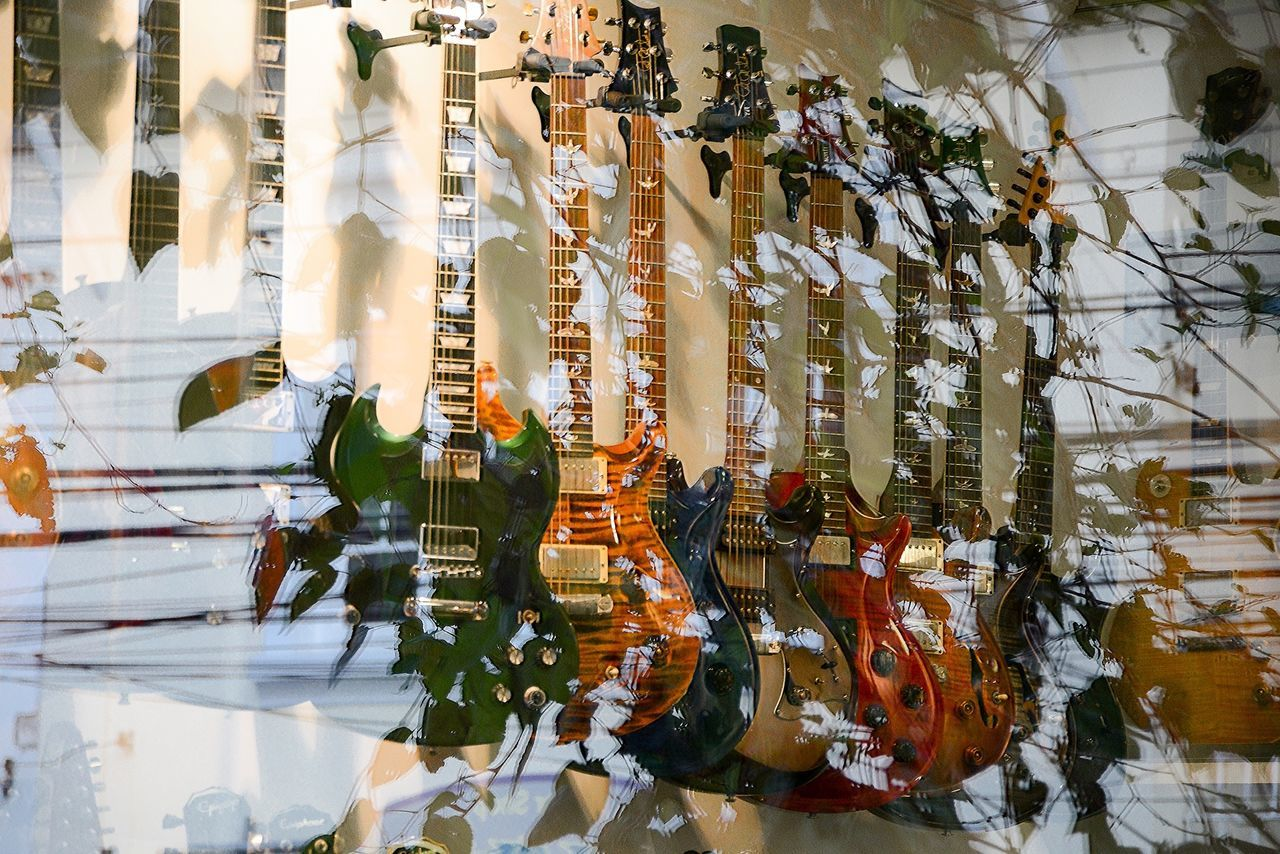 Guitars on display in store with reflection on glass window