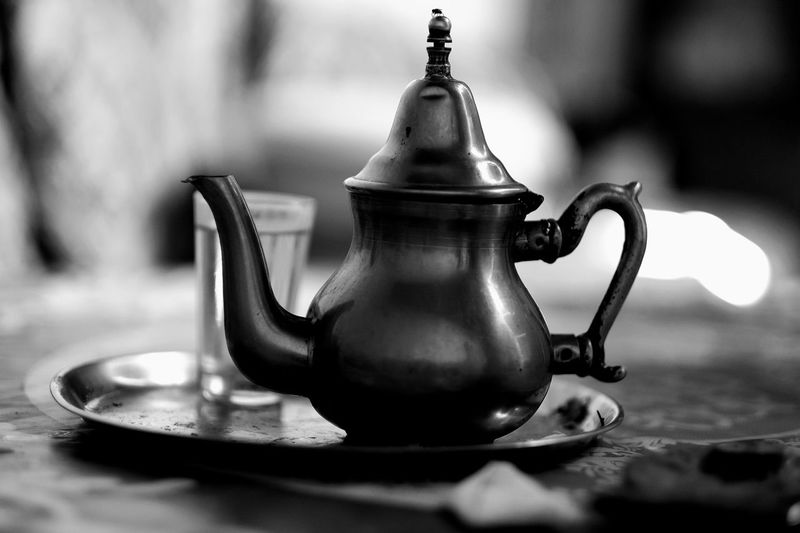 Close-up of teapot and glass on tray