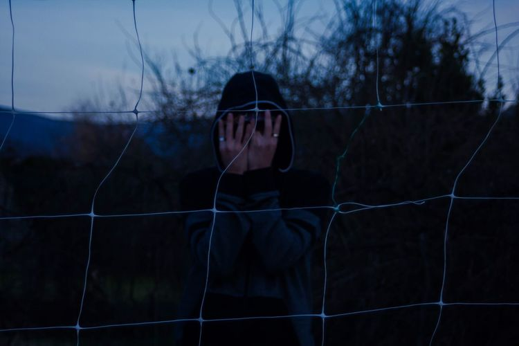Man hiding face with hands seen through net during dusk