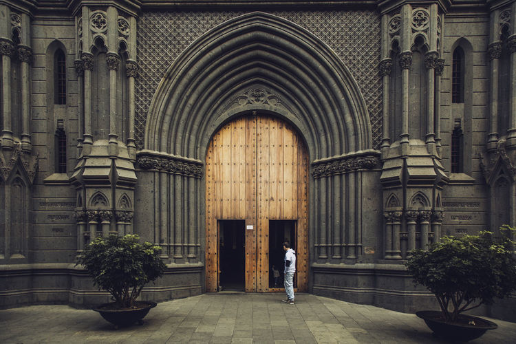 Architecture Built Structure Building Arch Building Exterior Place Of Worship Real People Spirituality One Person Religion Full Length Belief Rear View Entrance Lifestyles Men Day Architectural Column Streetphotography History Historic Historical Building Old Door Alone