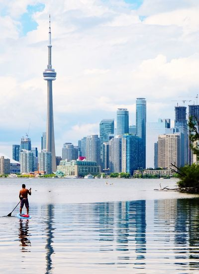 Man Paddleboarding On Lake Against Cityscape