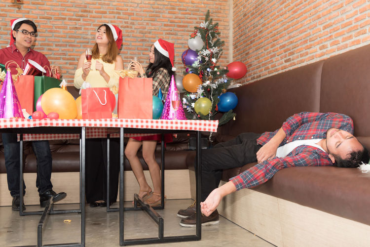 Drunk man lying on sofa while friends celebrating christmas