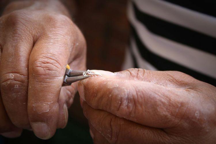 Cropped Hands On Man Turning Wire With Tweezers