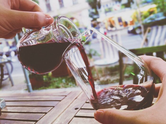 Close-up of pouring wine into glass outdoors