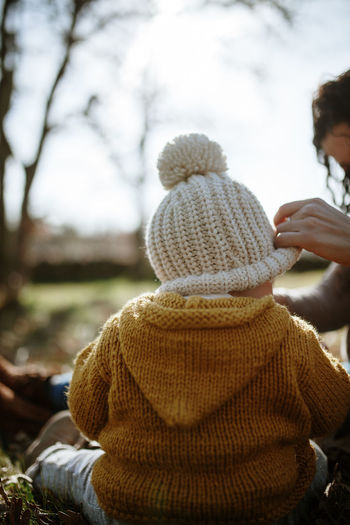 Wool Cap Baby Mother & Daughter Motherhood Cold Temperature Warm Clothing One Person Clothing Winter Rear View Knit Hat Lifestyles Sweater Outdoors Glove Women Real People Nature Family Matters Family With One Child Love Togetherness Leisure Activity Tree